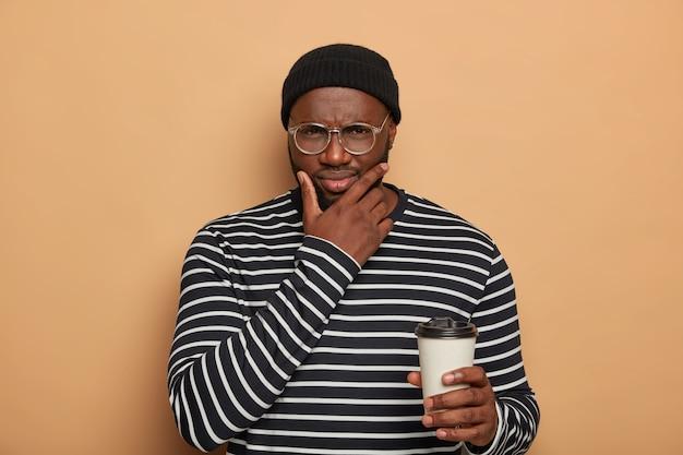 Nachdenklicher missfallener junger mann hält kinn, das kaffee zum mitnehmen hält