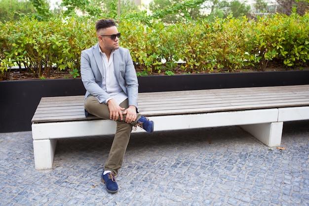 Nachdenklicher moderner mann, der im stadtpark stillsteht