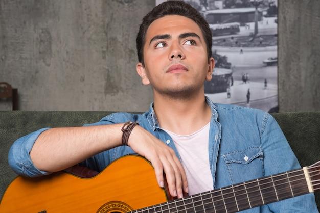 Nachdenklicher musiker, der eine schöne gitarre hält und auf sofa sitzt. hochwertiges foto
