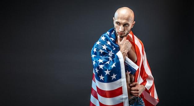 Nachdenklicher muskulöser mann, der amerikanische flagge trägt