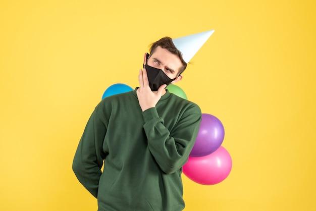 Nachdenklicher nachdenklicher junger mann der ansicht mit partykappe und bunten luftballons, die auf gelb stehen