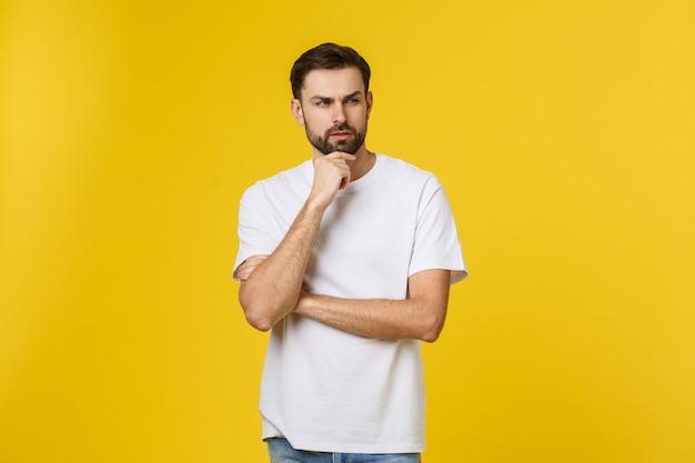 Nachdenklicher neugieriger mann, der oben in der denkenden haltung versucht, die wahl oder entscheidung lokalisiert auf gelber wand zu treffen schaut.