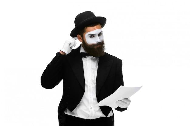Nachdenklicher pantomime als geschäftsmann, der die liste des papiers liest