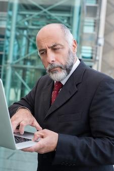 Nachdenklicher reifer mann, der laptop auf straße verwendet