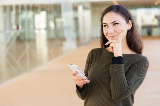 Nachdenklicher schlauer telefonbenutzer, der über mitteilung denkt