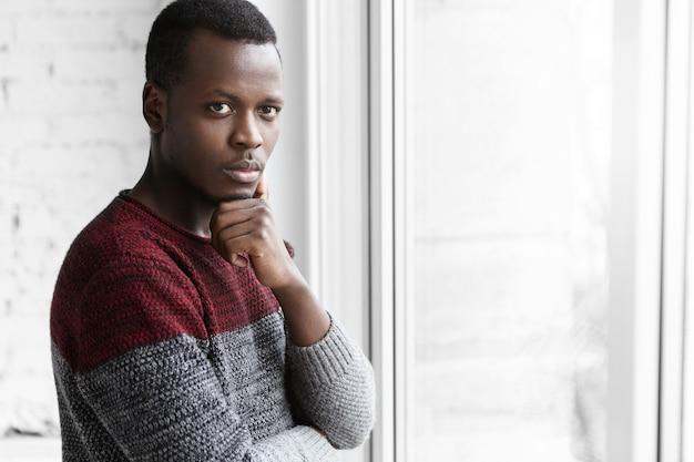 Nachdenklicher schöner afrikanischer architekt im pullover, der nachdenklichen blick hat