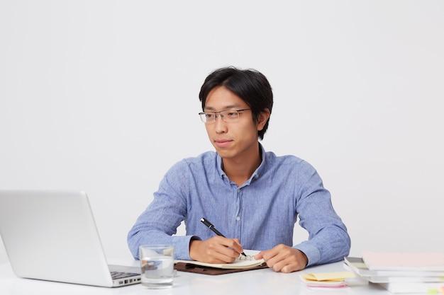 Nachdenklicher schöner junger asiatischer geschäftsmann in den gläsern, die im notizbuch schreiben, das am tisch mit laptop über weißer wand arbeitet