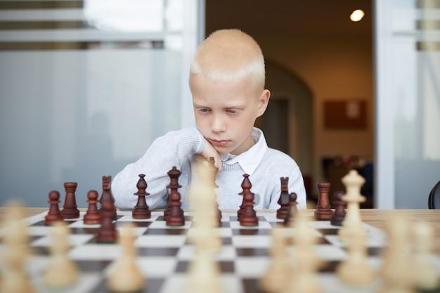 Nachdenklicher schüler, der schach spielt
