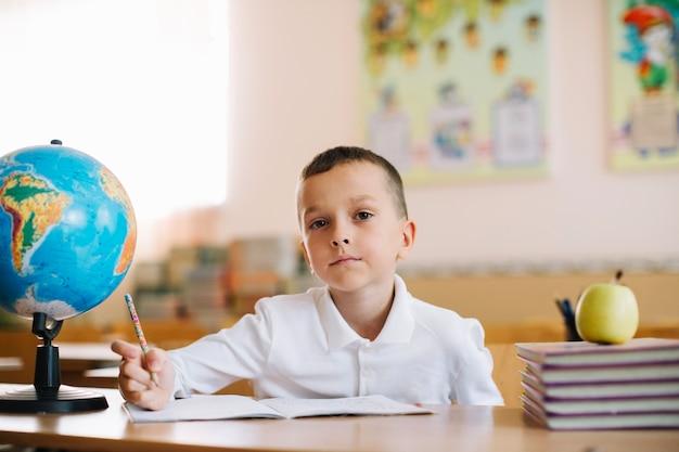 Nachdenklicher schüler mit globus auf dem schreibtisch