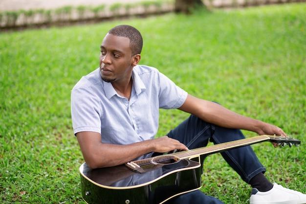 Nachdenklicher schwarzer mann, der gitarre hält und auf gras sitzt