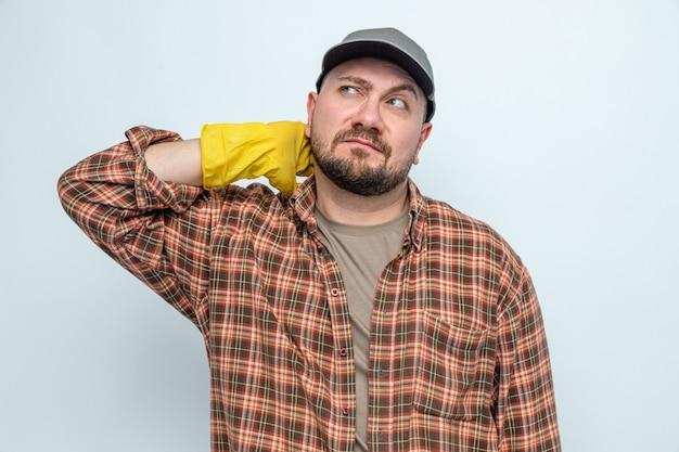 Nachdenklicher slawischer putzmann mit gummihandschuhen, der auf die seite schaut