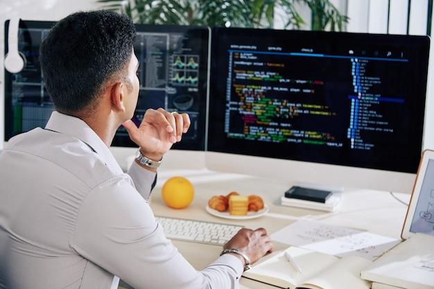 Nachdenklicher softwareentwickler, der an seinem schreibtisch arbeitet und fehler im programmiercode auf dem computerbildschirm überprüft