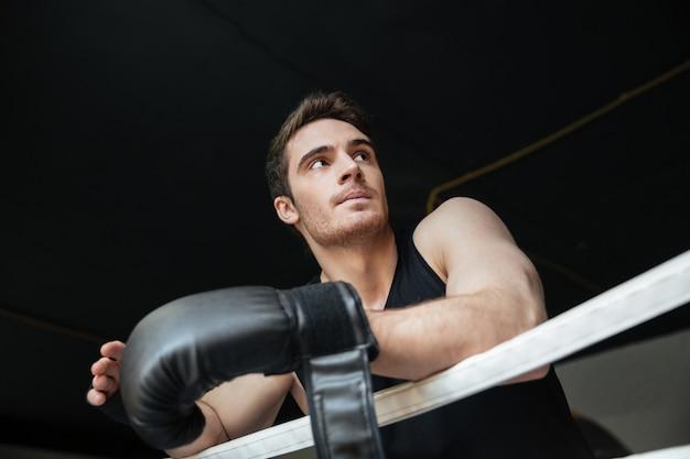 Nachdenklicher sportler, der auf ring steht
