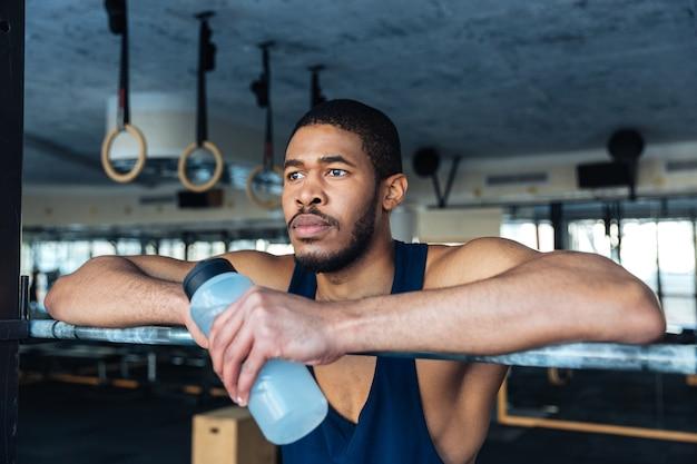 Nachdenklicher sportler, der eine flasche mit wasser hält und sich im fitnessstudio ausruht