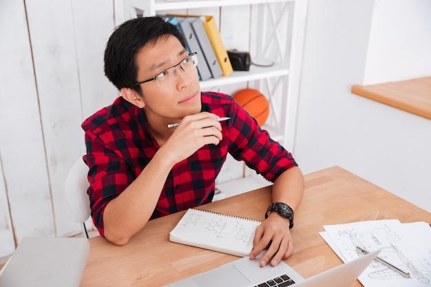 Nachdenklicher student, der an seinem laptop im klassenzimmer arbeitet