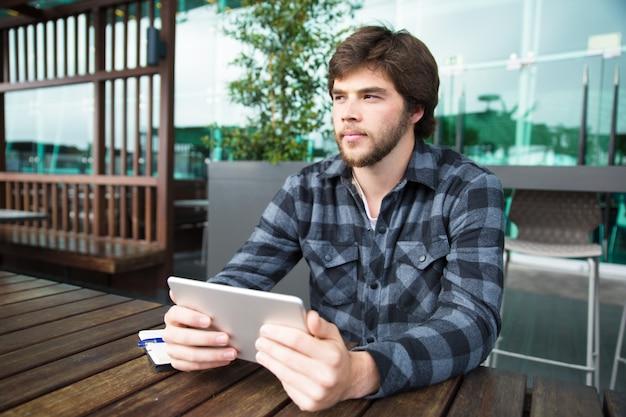 Nachdenklicher student, der tablette verwendet