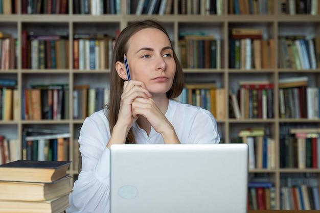 Nachdenklicher student sitzt in der bibliothek und denkt an prüfungen, die einen bleistift in den händen halten