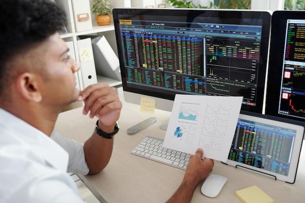 Nachdenklicher trader, der die geschäftstätigkeit des unternehmens analysiert, bevor er eine entscheidung über den kauf oder verkauf von aktien trifft