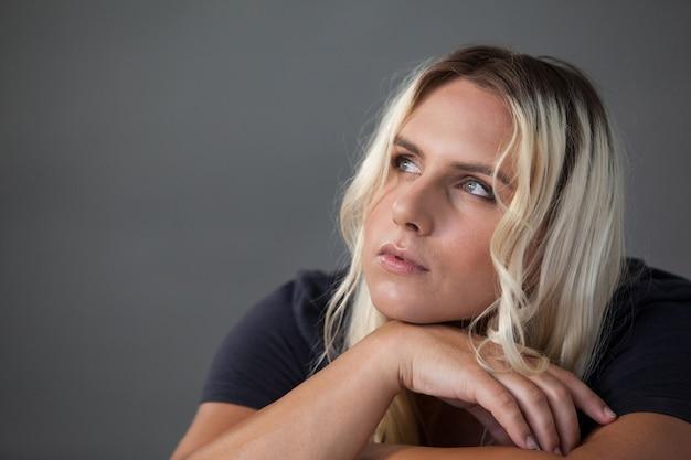 Nachdenklicher transgender, der sich auf stuhl stützt