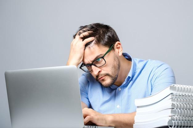 Nachdenklicher trauriger mann, der mit laptop am tisch sitzt
