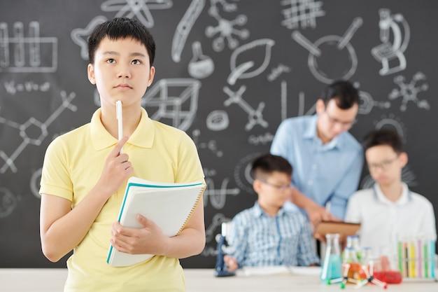 Nachdenklicher vietnamesischer schüler mit heft und stift, der chemiegleichungen im naturwissenschaftlichen unterricht löst