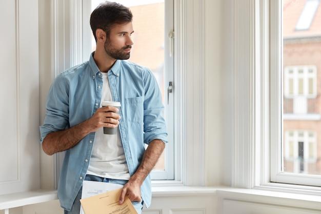 Nachdenklicher vorsitzender mit dunklen borsten, gekleidet in ein stilvolles hemd, hält kaffee zum mitnehmen, papiere, studiensteuern