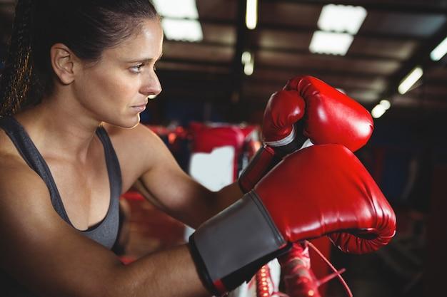 Nachdenklicher weiblicher boxer, der sich auf boxring stützt