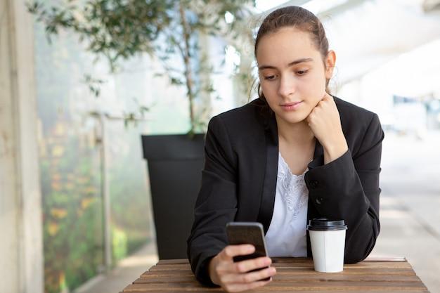 Nachdenklicher weiblicher büroangestellter, der neue bewegliche app prüft
