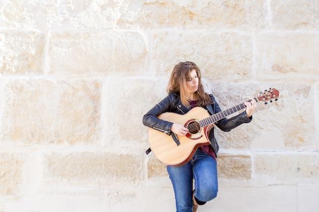 Nachdenklicher weiblicher straßen-musiker, der gitarre spielt
