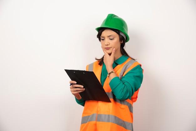 Nachdenklicher weiblicher wirtschaftsingenieur in uniform mit zwischenablage auf weißem hintergrund.