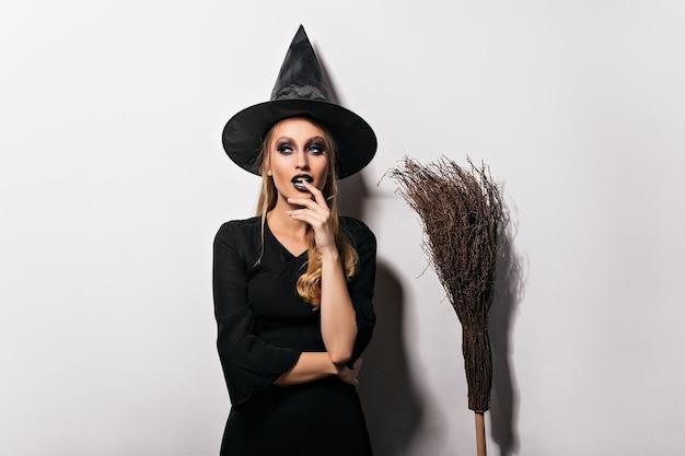 Nachdenklicher weiblicher zauberer, der auf weißer wand aufwirft. sinnliche junge hexe im schwarzen hut, der neben besen steht.