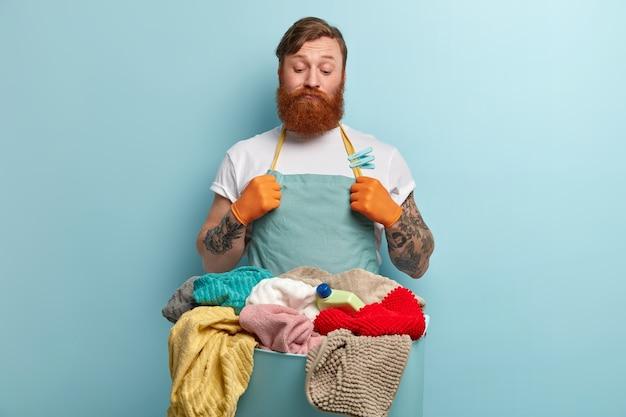Nachdenklicher zweifelhafter unentschlossener mann mit dickem ingwerbart, schaut sich die wäsche an, weiß nicht, wie man sich wäscht, will nicht waschen