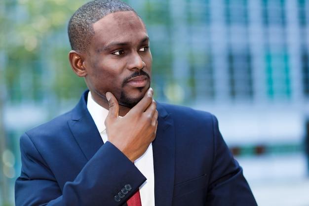 Nachdenkliches afrikanisches managerporträt ina moderne städtische einstellung
