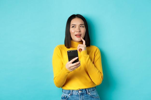 Nachdenkliches asiatisches mädchen, das smartphone hält und überlegt, was man online bestellt, über blauem hintergrund stehend.