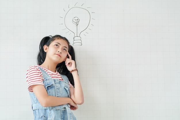 Nachdenkliches asiatisches teenager-mädchen, das an der weißen wand mit glühbirnenzeichnung steht