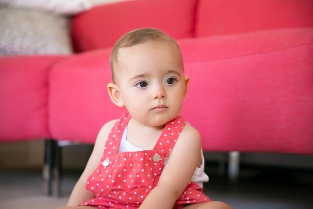 Nachdenkliches baby, das auf boden im wohnzimmer sitzt und an etwas denkt. ernstes kleines mädchen in roten latzhose-shorts, die weg schauen und nahe sofa sitzen. wochenende, kindheit und zuhause sein konzept
