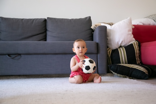 Nachdenkliches baby, das fußball hält, barfuß auf teppich sitzt und wegschaut. schönes kleinkind in roten latzhose shorts spielen zu hause in der nähe von sofa. ferien-, wochenend- und kindheitskonzept