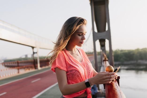 Nachdenkliches blondes mädchen, das sms während des stehens in der nähe von schlackenweg schreibt. schöne frau in der freizeitkleidung, die nach dem training im freien aufwirft.