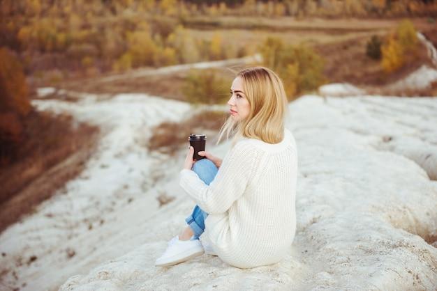 Nachdenkliches einsames mädchen, das in den bergen mit einer tasse kaffee sitzt, herbstzeit