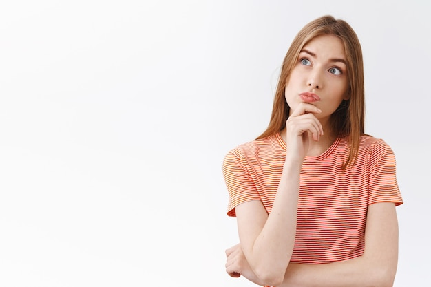 Nachdenkliches fasziniertes junges blondes mädchen in gestreiftem t-shirt, kinn berühren und neugierig schmollend, obere linke ecke fasziniert und unsicher schauen, wahl treffen, über entscheidung nachdenken, weißer hintergrund