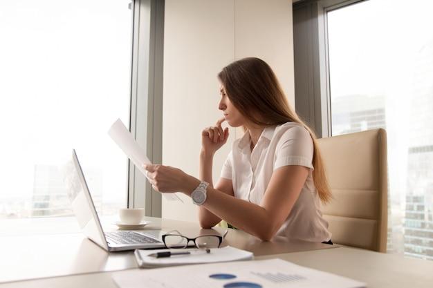 Nachdenkliches geschäftsfraulesedokument im büro