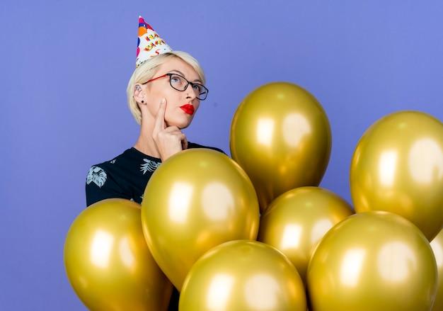 Nachdenkliches junges blondes parteimädchen, das brille und geburtstagskappe trägt, die hinter ballons steht, die gesicht berühren und lokalisiert auf lila hintergrund suchen