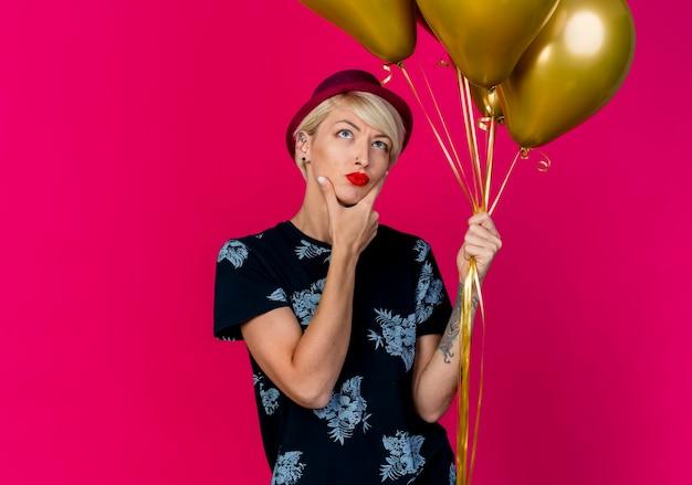 Nachdenkliches junges blondes partygirl, das partyhut hält, der ballons hält, die kinn berühren, lokalisiert auf purpurrotem hintergrund mit kopienraum