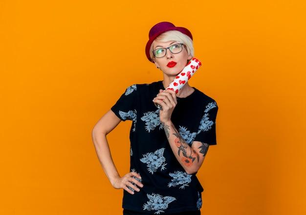 Nachdenkliches junges blondes partygirl, das partyhut und brille trägt, die hand auf taille hält, die das gesicht berührt, das gesicht mit konfettikanone berührt, lokalisiert auf orange hintergrund mit kopienraum