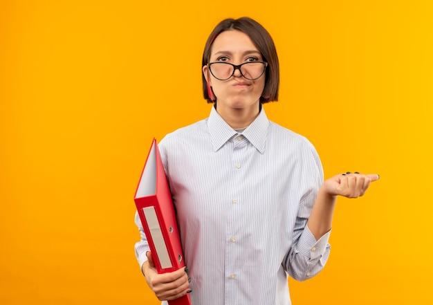 Nachdenkliches junges callcenter-mädchen, das eine brille hält, die ordner zeigt, der auf seite lokalisiert auf orange wand zeigt Kostenlose Fotos