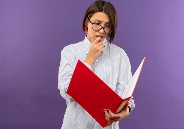 Nachdenkliches junges callcenter-mädchen, das eine brille trägt, die ordner hält und betrachtet und ihren finger lokalisiert auf lila wand beißt