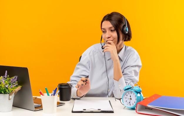 Nachdenkliches junges callcenter-mädchen, das headset trägt, sitzt am schreibtisch mit arbeitswerkzeugen, die finger auf lippen setzen, die laptop lokalisiert auf orange wand betrachten
