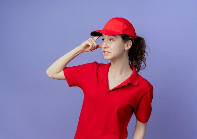 Nachdenkliches junges hübsches liefermädchen, das rote uniform und kappe trägt, die finger auf kopf setzen, der seite lokalisiert auf lila hintergrund mit kopienraum betrachtet