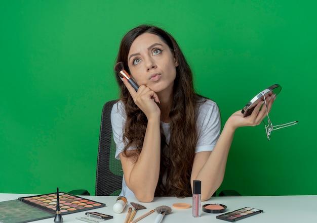 Nachdenkliches junges hübsches mädchen, das am make-up-tisch mit make-up-werkzeugen hält, die spiegel halten und gesicht mit errötendem pinsel berühren, der lokal auf grünem hintergrund schaut