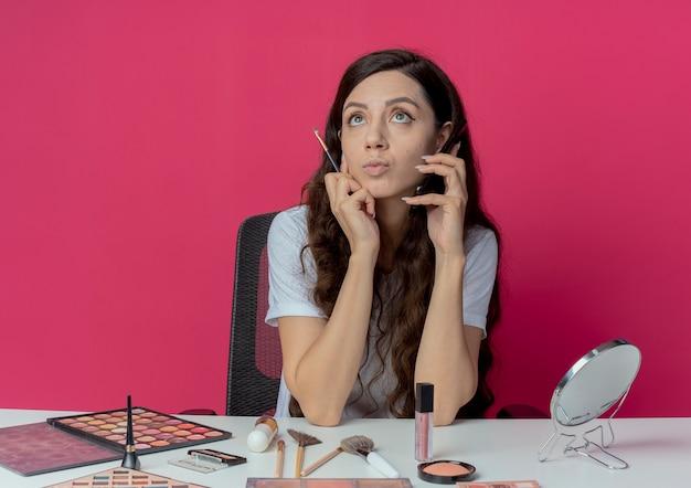 Nachdenkliches junges hübsches mädchen, das am make-up-tisch mit make-up-werkzeugen sitzt, die am telefon sprechen und make-up-pinsel halten und lokal auf purpurrotem hintergrund suchen